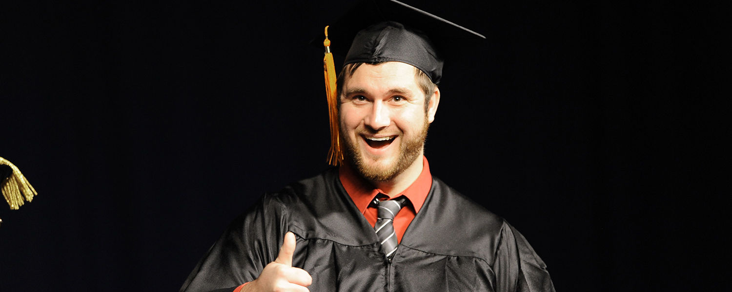 """A graduating student flashes the """"thumb's up"""" sign to his parents after receiving his diploma Saturday morning, in the Memorial Athletic and Convocation Center."""