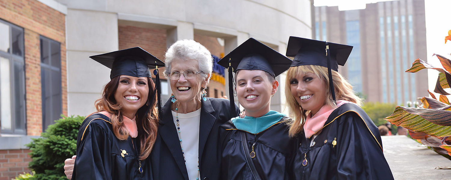 Three sisters, who all graduated with their master's degrees during Kent State's Summer 2016 Commencement ceremony, pose for a photo with their grandmother.