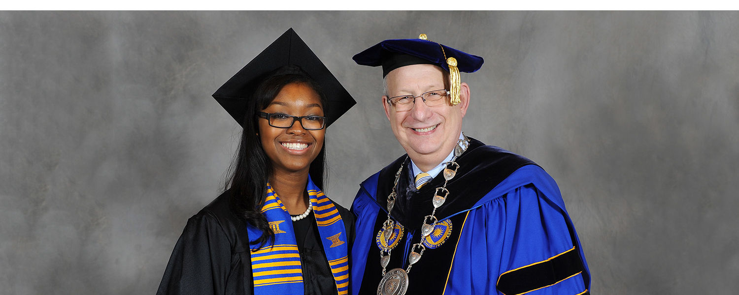 A Kent State graduate poses for a photograph with President Lester A. Lefton following commencement ceremonies in the Memorial Athletic and Convocation Center.