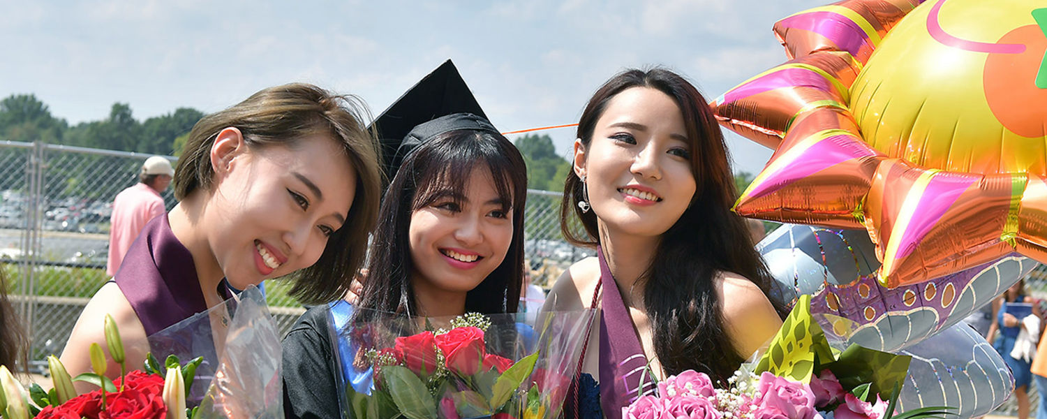 Three graduates of the fashion program pose for photos outside the MAC Center following Kent State's Summer 2016 Commencement ceremony.