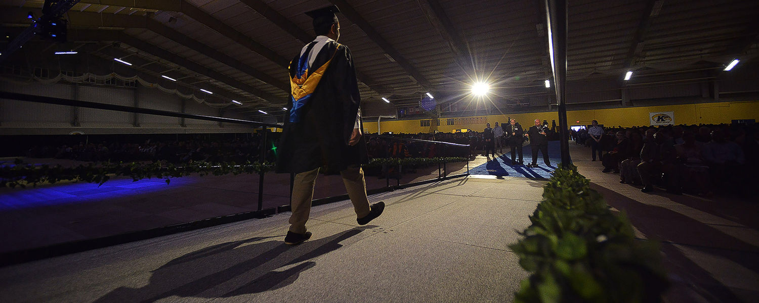 A master's recipient walks down the ramp in the Kent State Field House after receiving his degree.