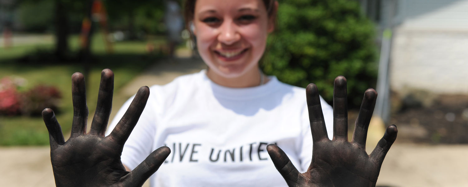 A Kent State student shows off her hands, stained from spreading mulch at the Freedom House in Kent.