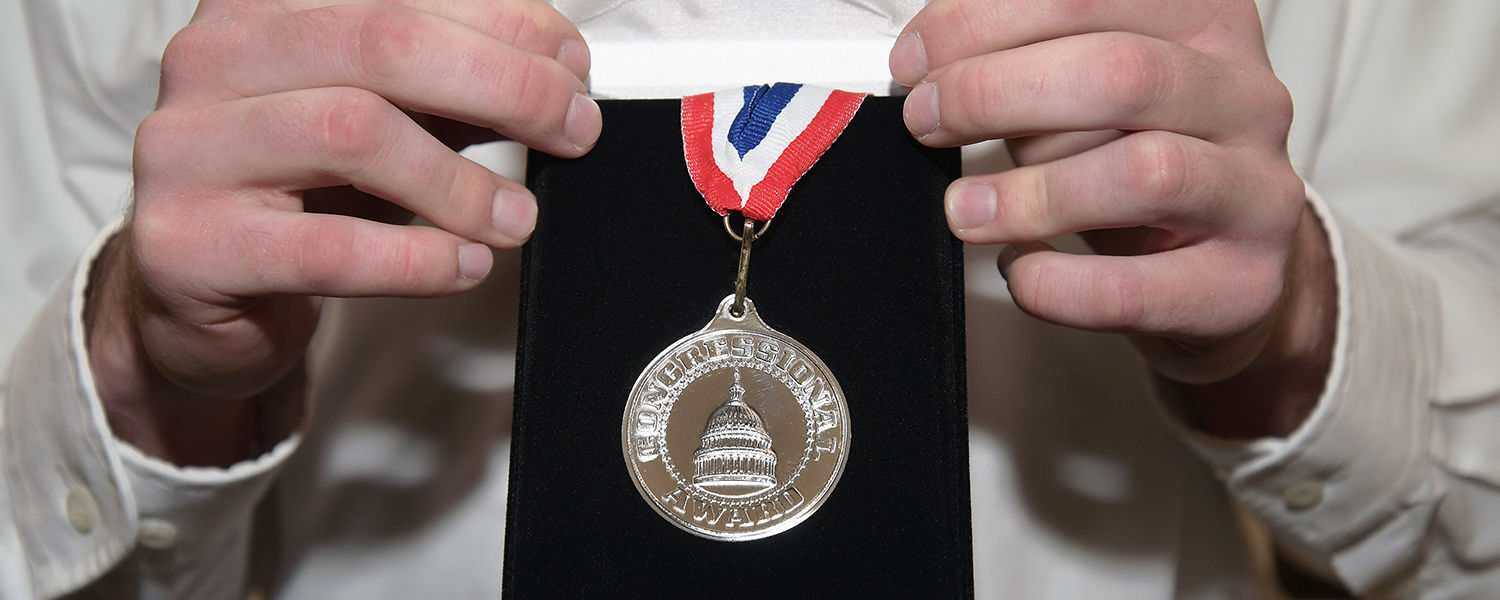 Hands holding the congressional silver medal