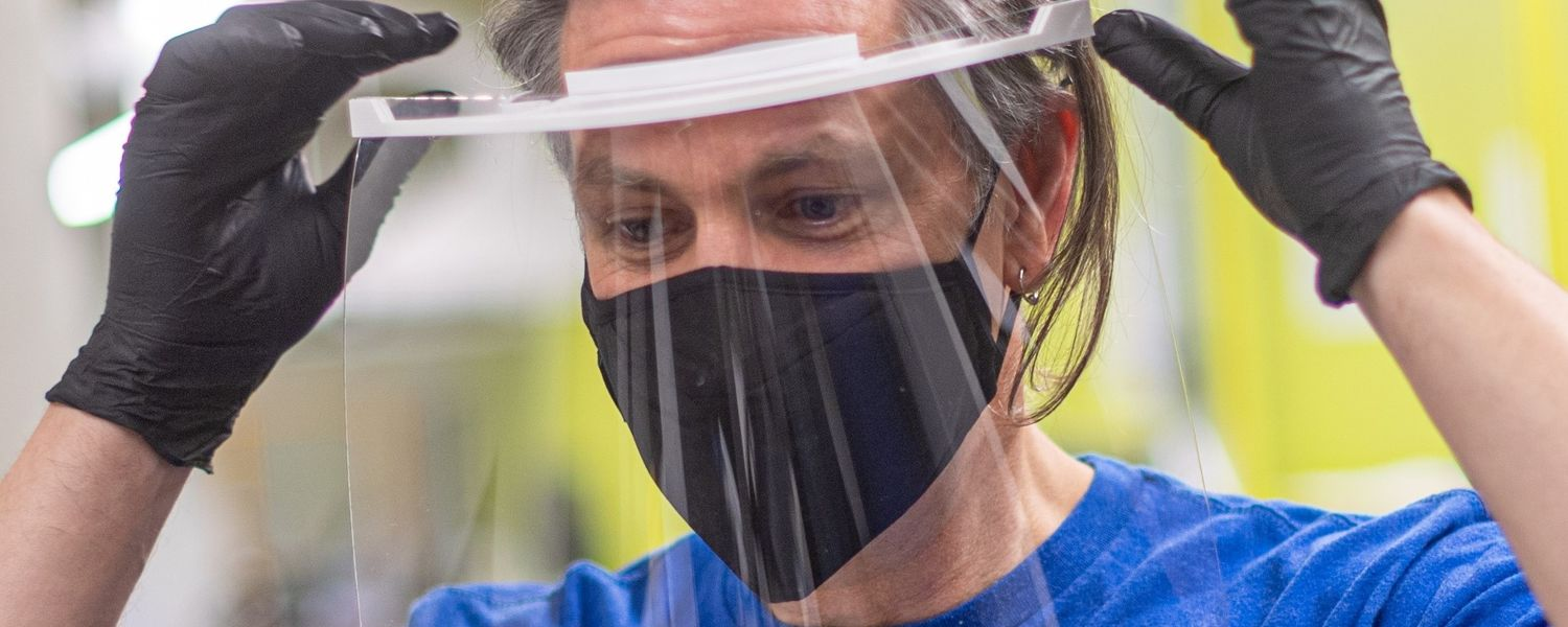J.R. Campbell, executive director of Kent State University's Design Innovation Initiative, tries on a face shield produced by the Kent State team.