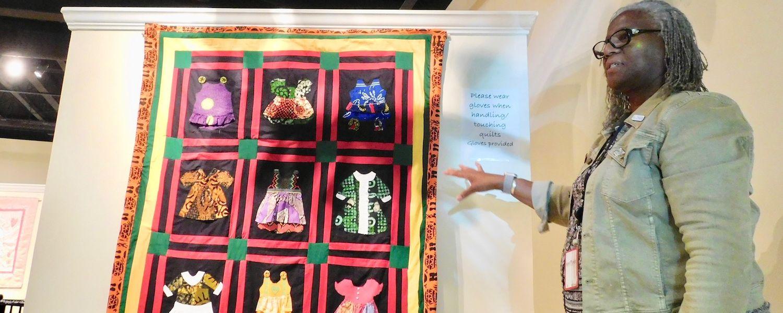 Professor Denise Harrison standing by #BlackLivesMatter Quilt Exhibit