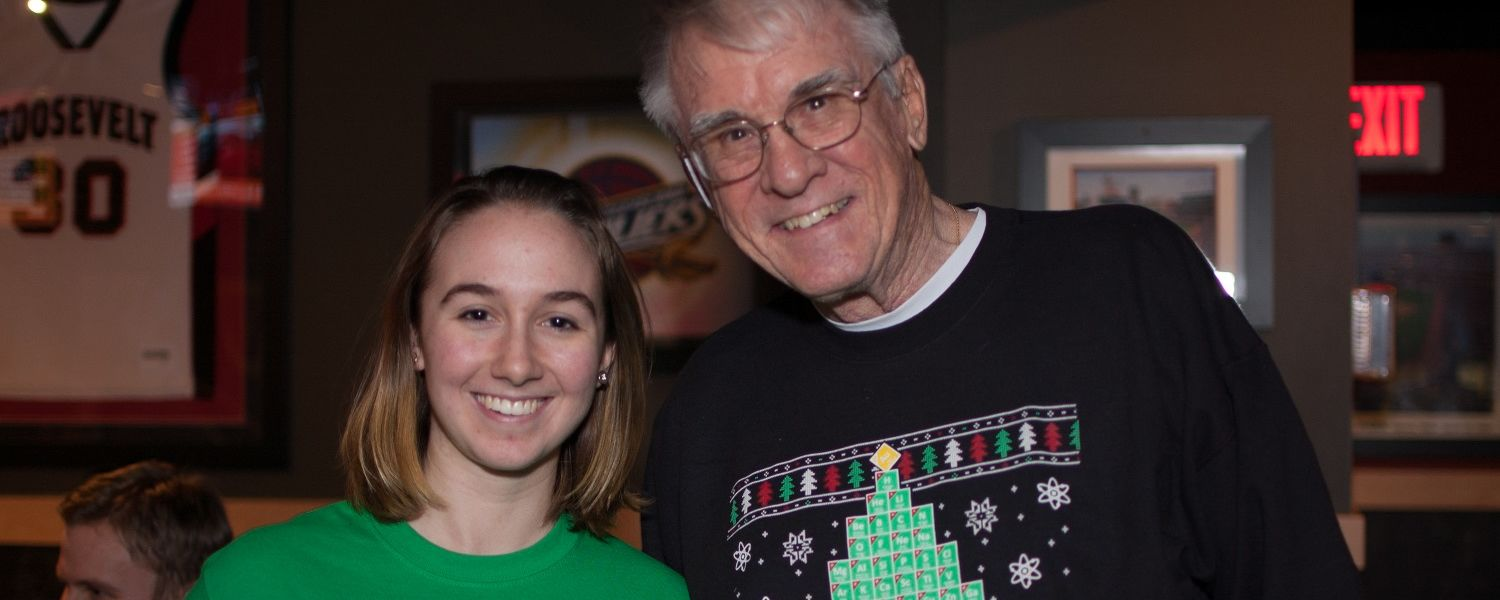 Attendees of the holiday party wear Christmas periodic table sweaters