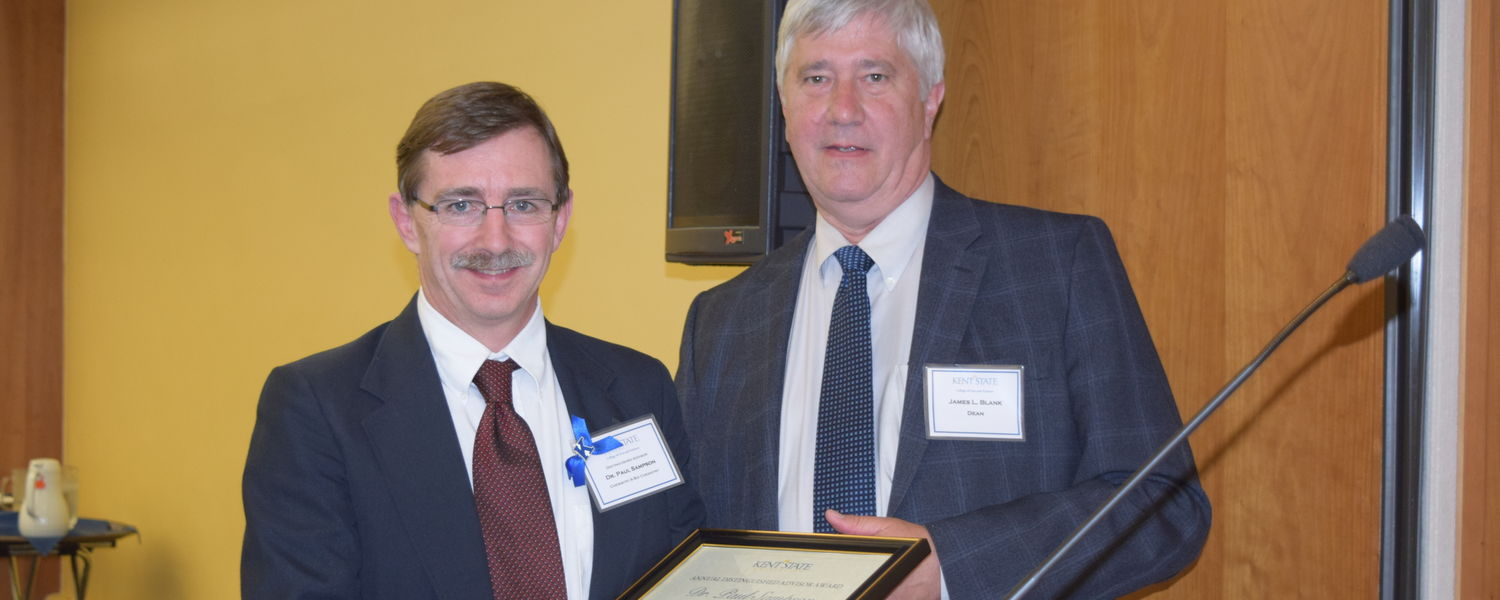 Dr. Paul Sampson, professor and assistant chair of Chemistry & Biochemistry (L) receives the Distinguished Advisor Award from James Blank, dean of the College of Arts and Sciences (R)