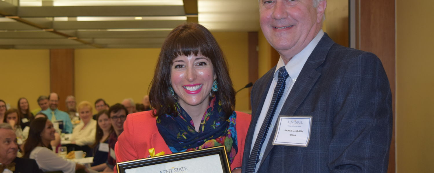 Dr. Kristin Stasiowski, professor of Italian Language and Literature, (L) receives the Distinguished Teacher Award from James Blank, dean of the College of Arts and Sciences (R)