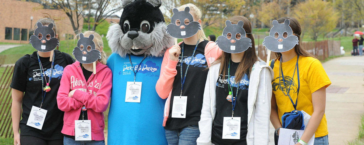 Kent State students and their siblings pose with cutout masks during Lil' Sibs Weekend last year.
