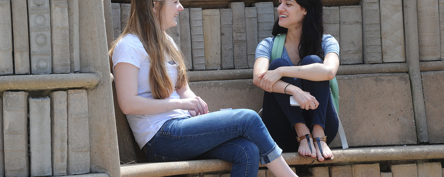 """Friends share a laugh while relaxing at the """"Behind the Brain Plaza"""" near Merrill  Hall."""