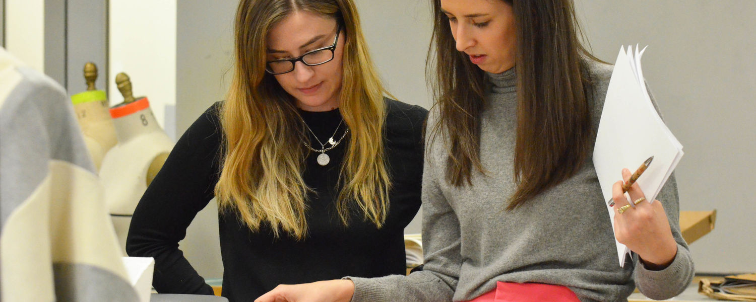 Kent Fashion alumni Erin Marvinney (pictured left) and Kendall Walter (right) review portfolios during 2019 senior design portfolio review.