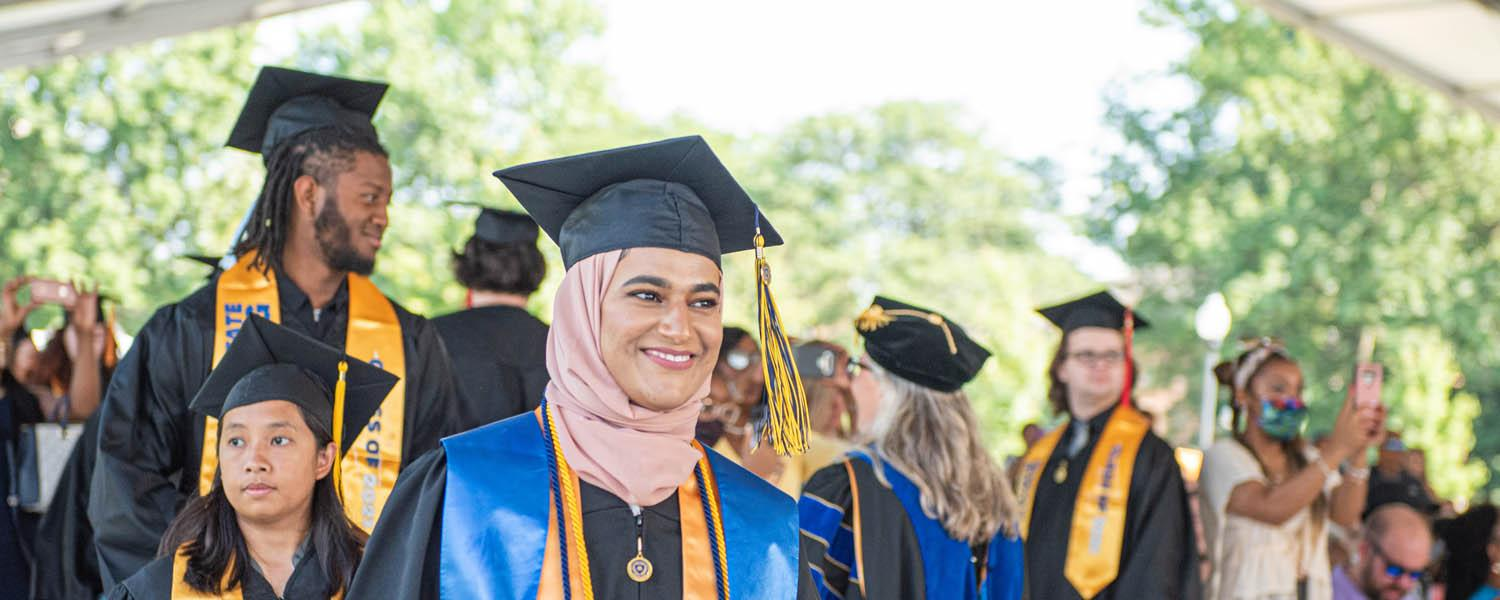 A new Kent State graduate smiles as she and her fellow graduates line up to walk across the stage and to receive their degrees during the undergraduate degree commencement ceremony.