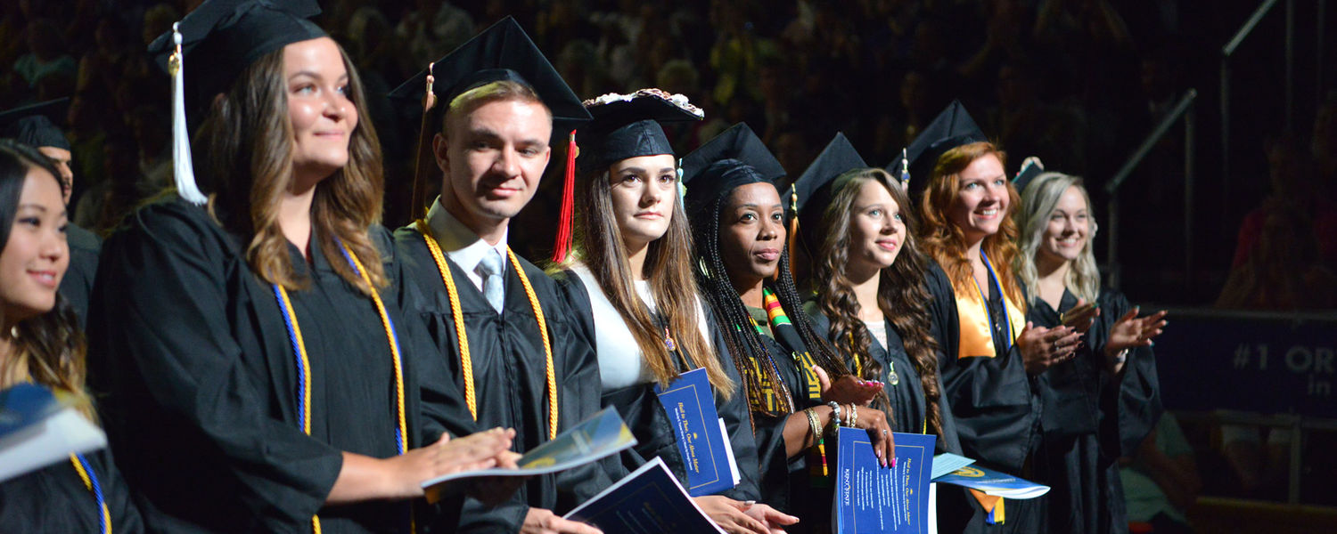 Stand and be recognized. Several members of Kent State's Class of 2019 stand together prior to receiving their degrees during the undergraduate commencement ceremony Aug. 17 at the Memorial Athletic and Convocation (MAC) Center.