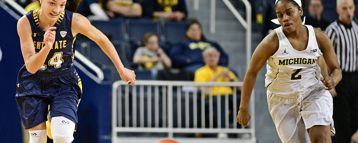 Kent State guard Alexa Golden and a Michigan player dash for a loose ball.