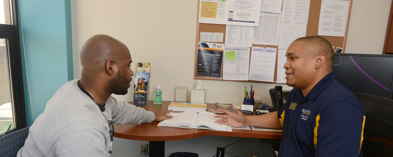 A student in the College of Business Administration goes over his class schedule with a college advisor.