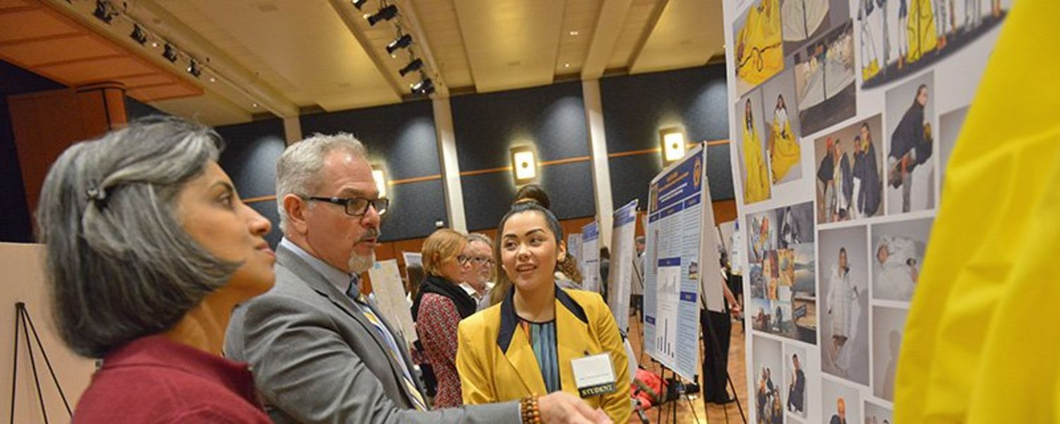 A student explains a visual summary of her research project to faculty judges at the Kent State Undergraduate Research Symposium. Students gain valuable experience in succinctly presenting and explaining their research.