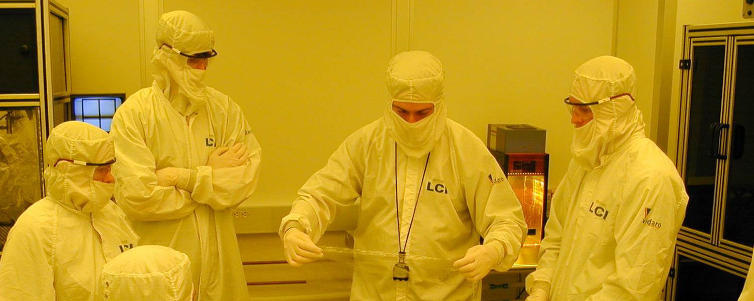 Douglas Bryant (center), manager of display engineering at Kent State's Liquid Crystal Institute, demonstrates a prototyping technique in the institute's clean room facility.