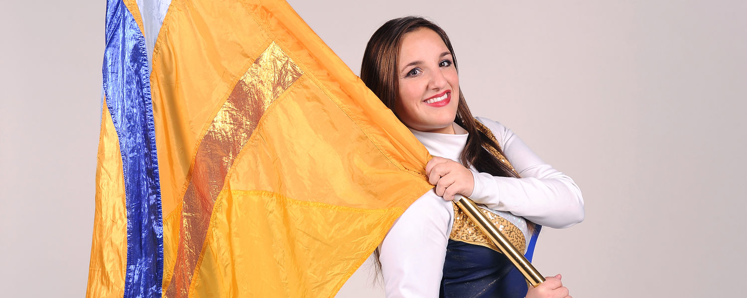 Katie Kimble, a member of the Kent State Marching Golden Flashes Colorguard, strikes a pose with the 6-foot-long flag she and her teammates work with at Kent State sporting and musical events.