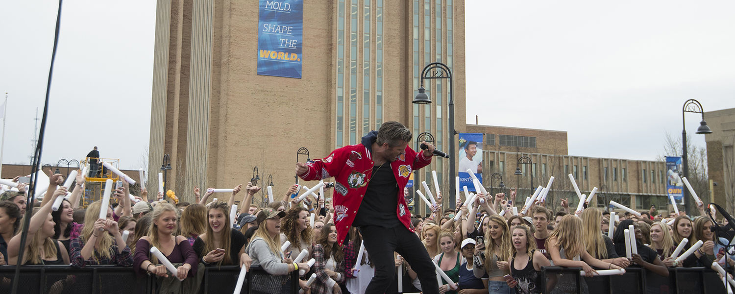 A member of 3OH!3 dances on the stage during FlashFest 2016 while Kent State students enjoy the performance