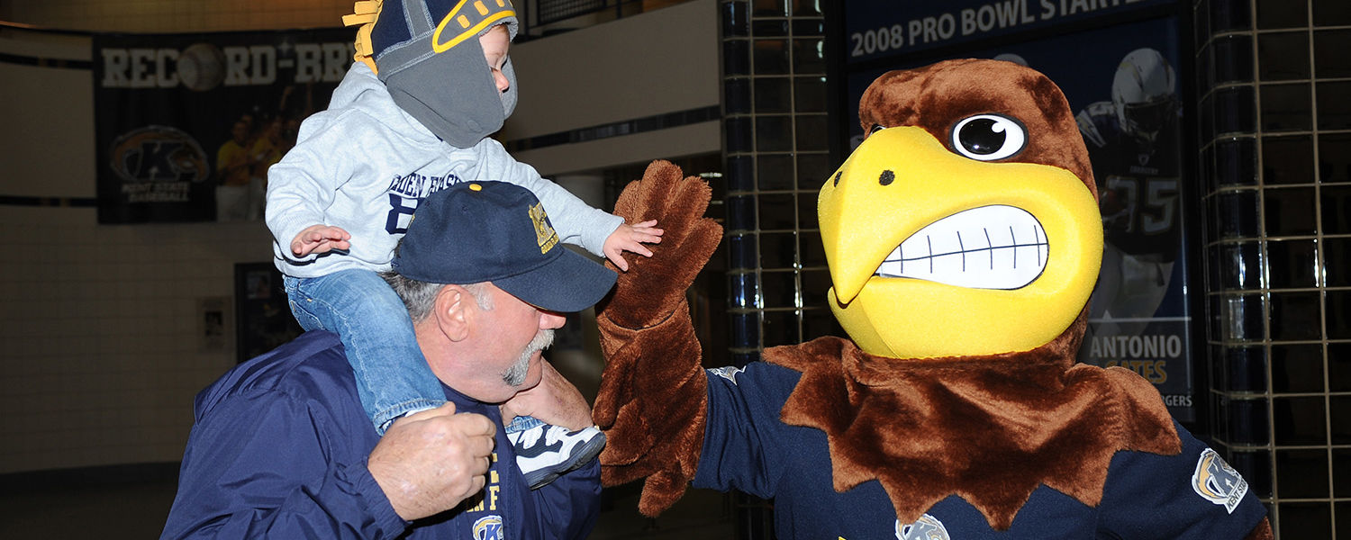 Flash, Kent State's mascot, high-fives 18-month-old Christopher Errico as he and his grandfather Pasquale Christopher (and parent of Kent State football team member Andrew Christopher) arrive for the football team send-off event in the MAC Center.