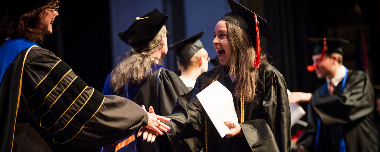 An excited graduate shakes hands with Dean Denise Seachrist at Commencement.