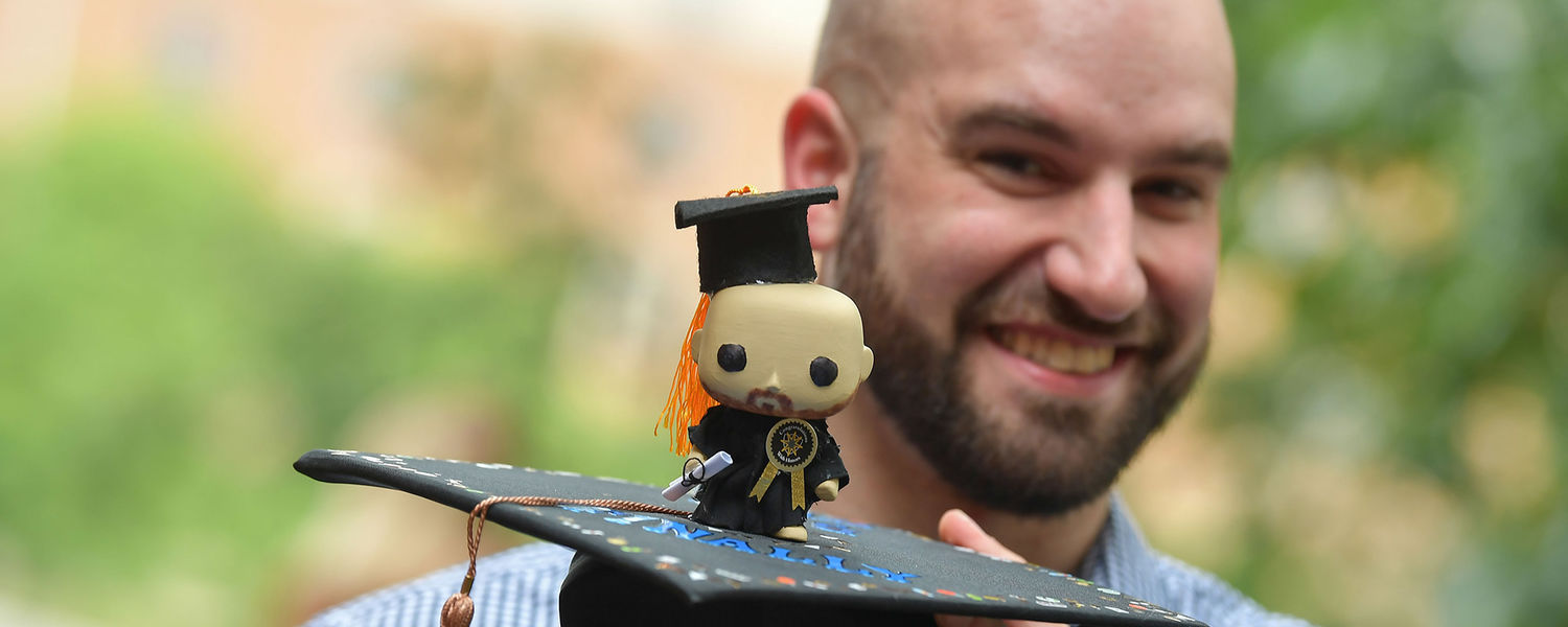 A College of Business Administration graduate shows of his mortar board while waiting for Kent State's Summer 2018 Commencement to start.