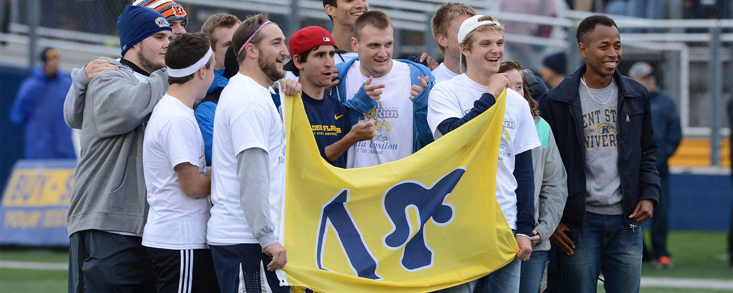 """Members of Delta Upsilon pose for a picture on the field at Dix Stadium following its 17th annual """"Flash N Duck Run"""" where fraternity members run the Homecoming game ball from """"The Rock"""" on Front Campus to the stadium."""