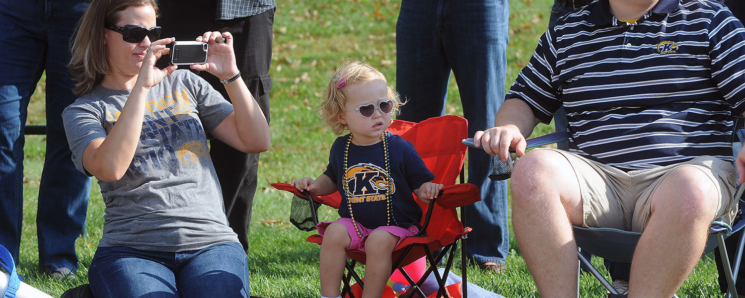Kent State alumni and families enjoy the view of the Homecoming parade near   Williamson Alumni Center.