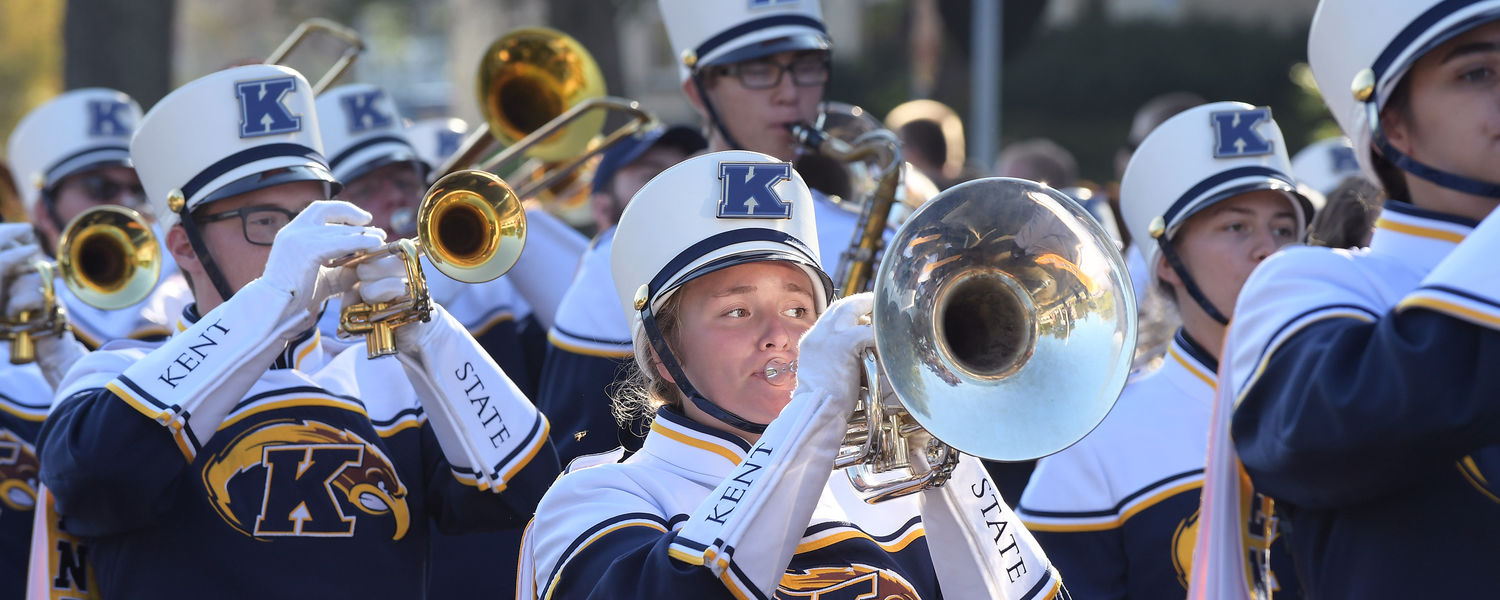 Members of the Kent State Marching Golden Flashes perform while moving along Main Street during the 2017 Homecoming Parade.