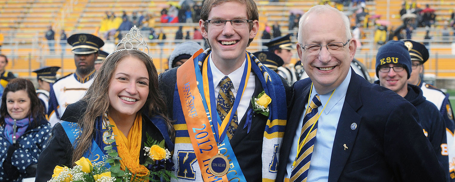 Kent State President Lester A. Lefton congratulates 2012 Homecoming King Tom Ream and Queen Ann Miller during the halftime ceremony at Dix Stadium.