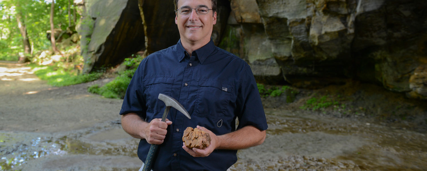 David Hacker, associate professor of geology at Kent State University at Trumbull, poses with some tools of his trade along a walking path at the Gorge Metro Park in Cuyahoga Falls, Ohio.