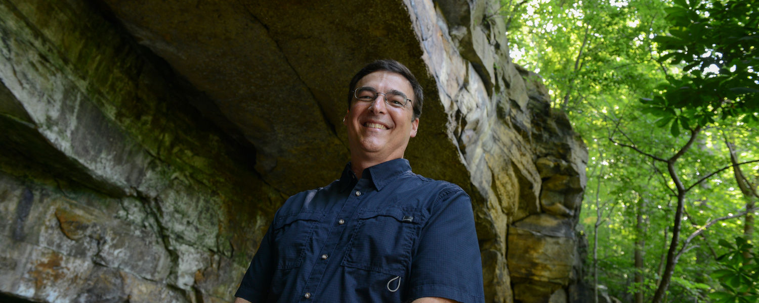 A rock formation at the Gorge Metro Park looms large over the head of David Hacker, associate professor of geology at Kent State University at Trumbull.