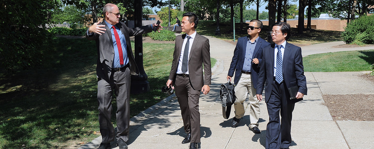 Todd Diacon (left), Kent State's senior vice president for academic affairs and provost, leads a tour from   the May 4 Memorial around Taylor Hall for members of the Hanoi University delegation.