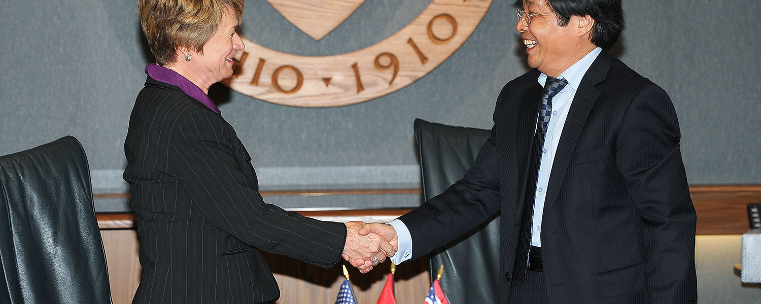 Kent State President Beverly Warren and Hanoi University President Nguyen Dinh Luan shake hands  after signing a historic agreement that will partner the universities.