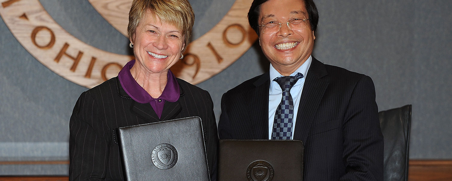 Kent State President Beverly Warren and Hanoi University President Nguyen Dinh Luan display their   copies of the signed agreements that will partner the universities.