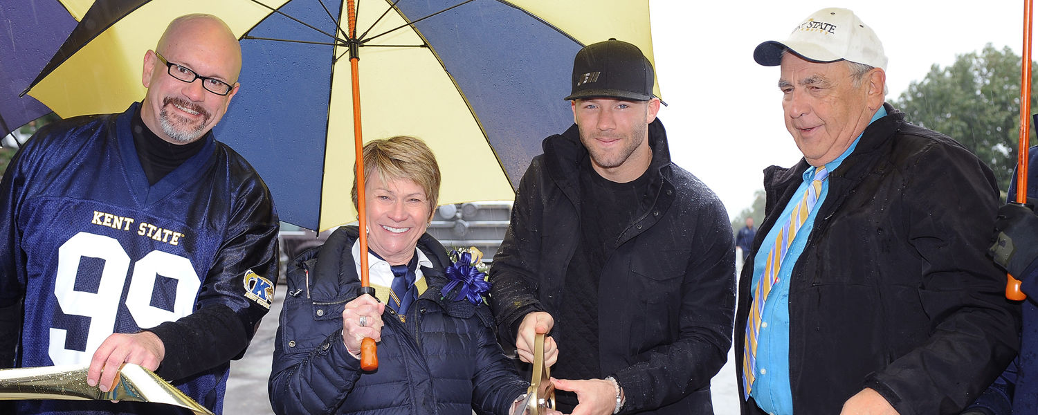 Kent State President Beverly Warren joins (left to right) Kent State English Professor Ed Dauterich, Parade Grand Marshal Julian Edelman and Kent Mayor Jerry Fiala in cutting the ribbon to officially start the 2015 Homecoming Parade.