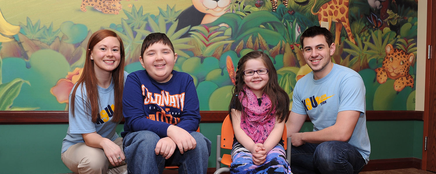Kent State students Abby Myers (left) and Andy Lovrak (right) pose for a photo with cancer survivors Jacob Sypert, age 11, and Adelyn Smith, age 6, in the playroom of the Reinberger Center at Akron Children's Hospital.