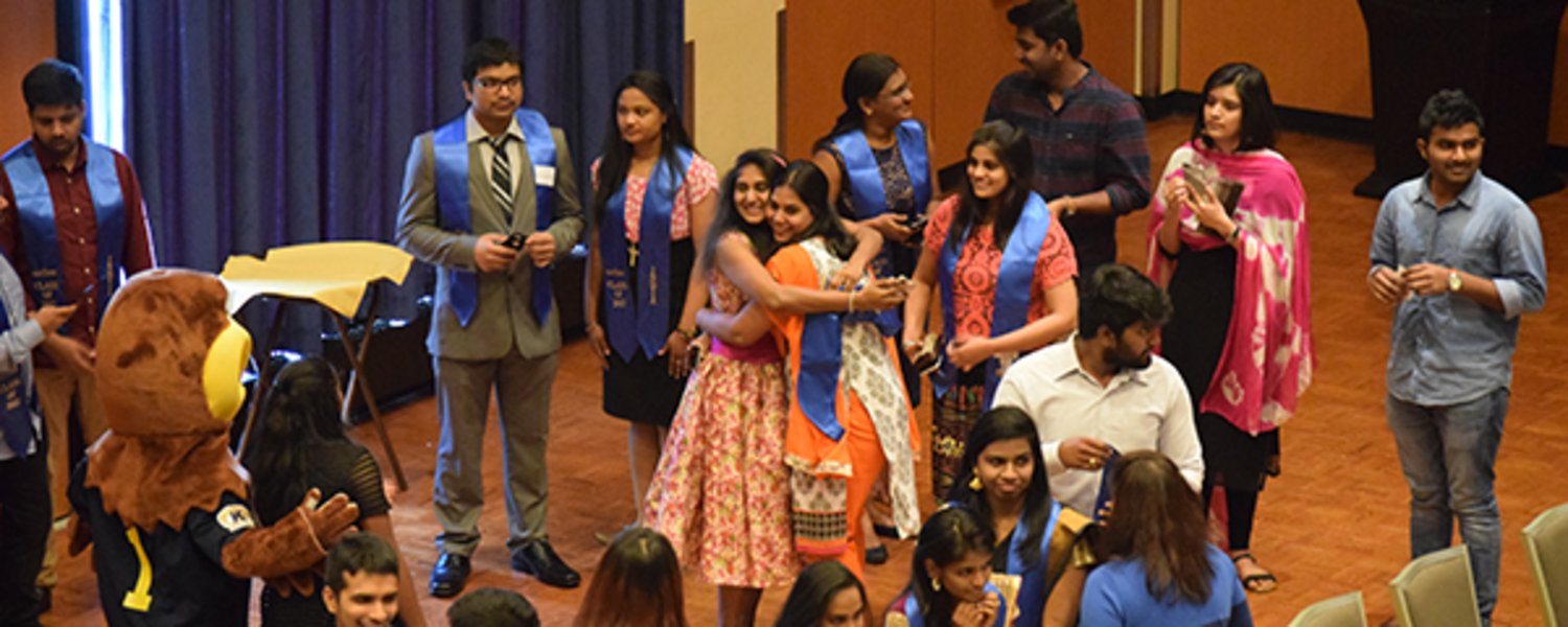 A group of students from India celebrate their graduation with a photo with Flash.