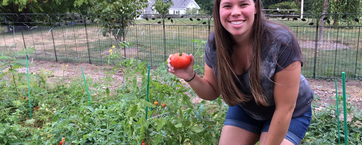 Kent State master's student Sarah Burns shows off a tomato from the garden behind Nixson Hall.