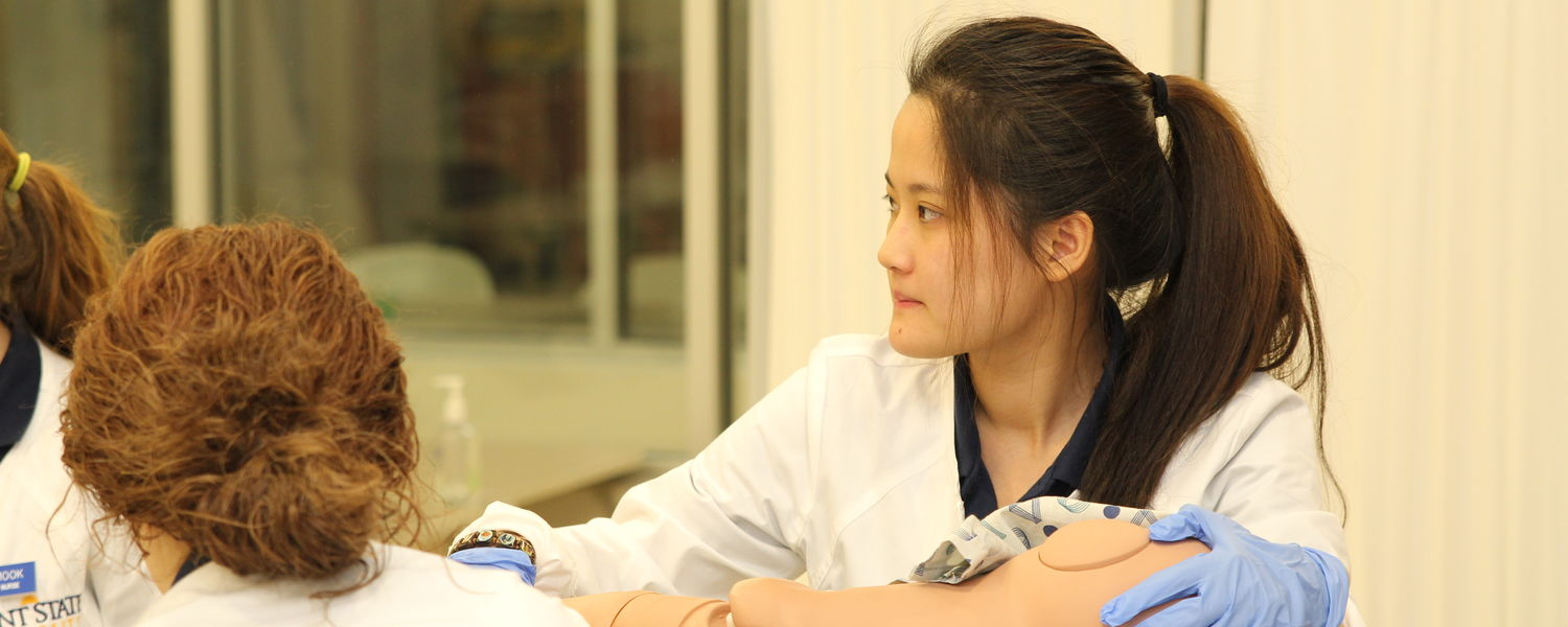 A Kent State Ashtabula nursing student participates in a class room activitiy with one of the campus's state-of-the-art patient simulators