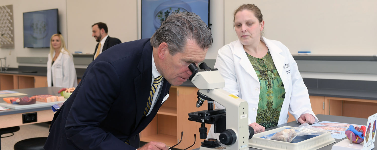 Sen. John Eklund examines science projects from Kent State graduate students in a laboratory in the new Integrated Sciences Building.