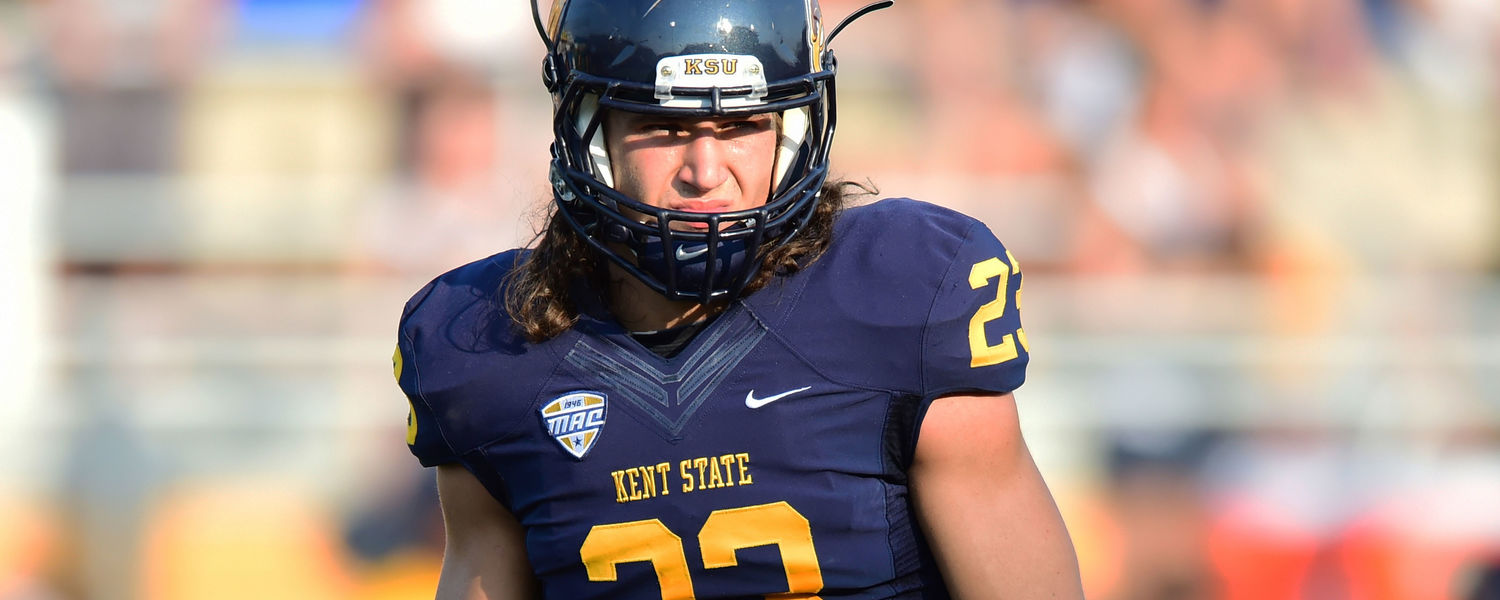 Kent State safety Jordan Italiano watches an opponent break from a huddle during a 2014 season game.