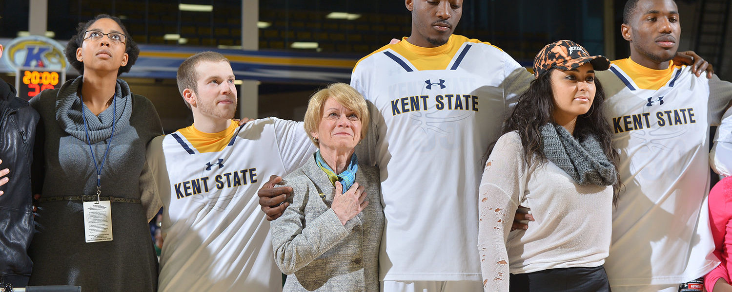 Kent State men's basketball players (left to right) Jon Fleming, Jimmy Hall and Deon Edwin stand in solidarity with fans of a different race selected from the crowd during the national anthem.