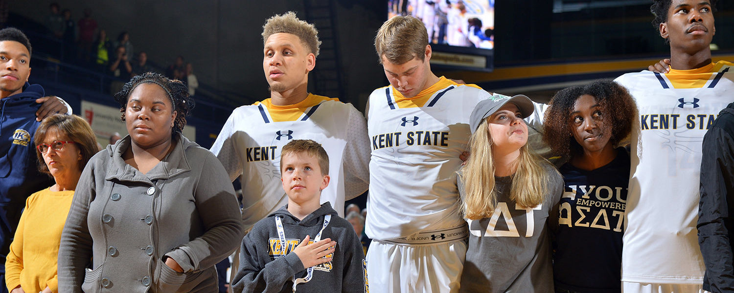 Kent State men's basketball players (left to right) Rosel Hurley, Jerrelle DeBerry, Mitch Peterson and Alonzo Walker stand in solidarity with fans of a different race selected from the crowd during the national anthem.