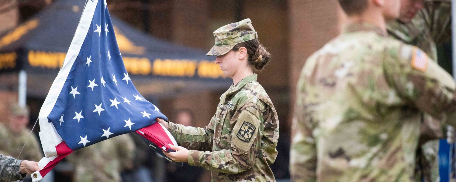 A joint color guard from Kent State's Army and Air Force ROTC programs conducts a flag-raising ceremony on the Student Green at Risman Plaza during the university's 2019 Veterans Day Commemoration.