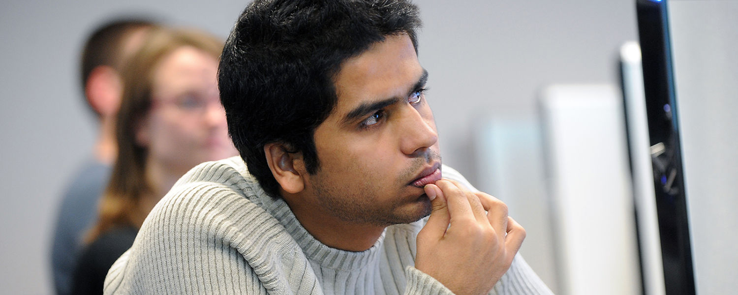 A student listens intently to a professor in Kent State's School of Journalism and Mass Communication.