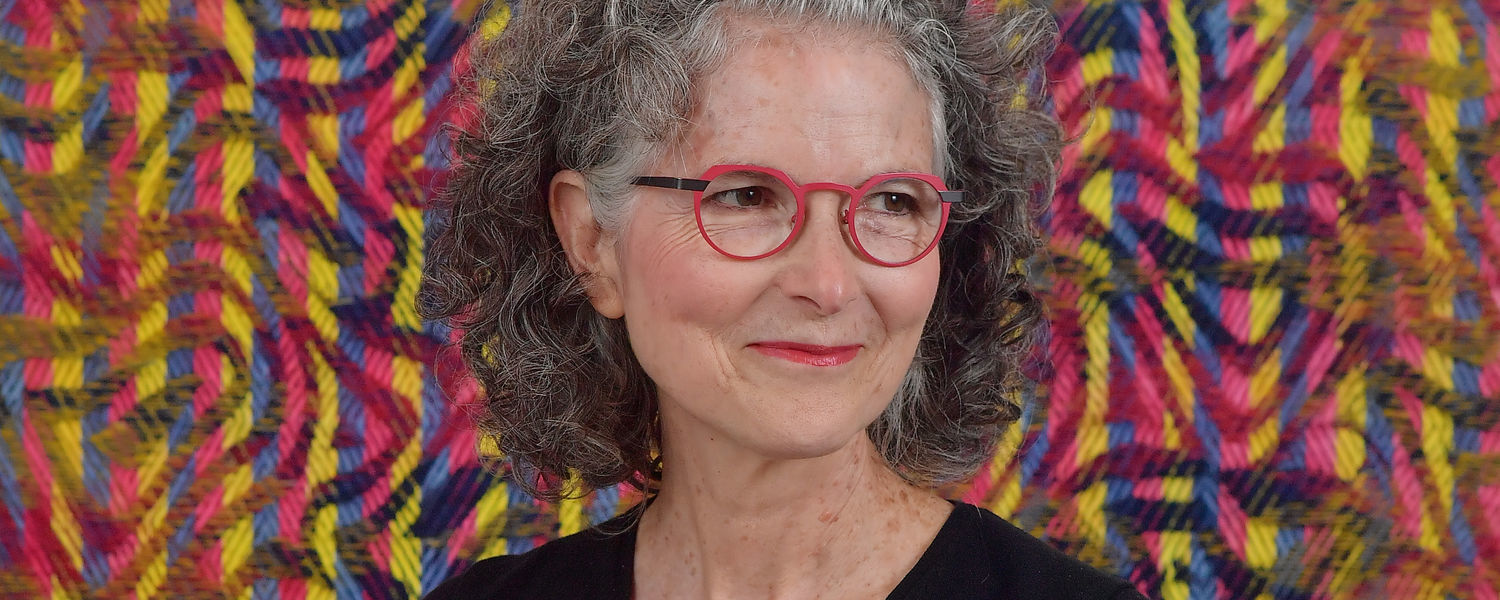Janice Lessman-Moss headshot in front of weaving