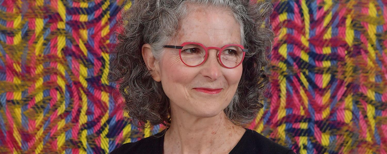 Janice Lessman-Moss headshot in front of weaving