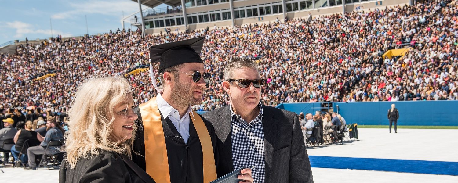 Julian Edelman poses for a picture with his parents after receiving his bachelor's degree at Kent State's 2019 One University Commencement.