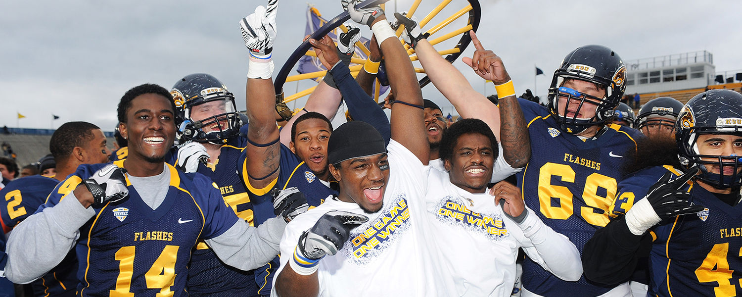 Kent State players charge onto the field to celebrate with the Wagon Wheel Trophy, after defeating the University of Akron 35-24 at Dix Stadium
